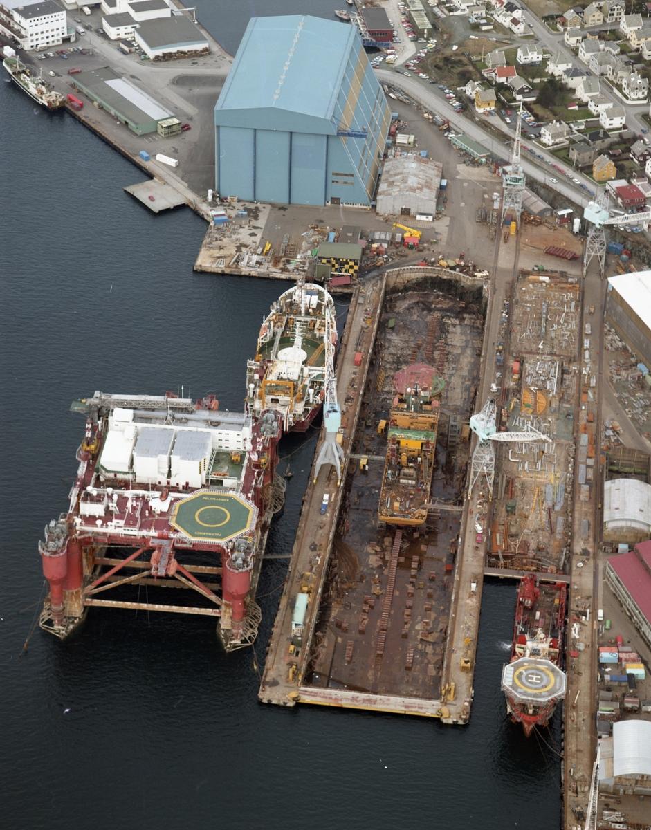 """Flyfoto H.M.V. Oversiktsfoto. Anleggsområdet med Nordsjøhallen i bakgrunnen. Platformen """"Polymariner"""" i forgrunnen."""