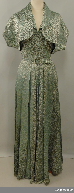 Selskapskjole, uten ermer, liten sjalskrage, overdel med omslag. Med bolero, belte og slep på kjolen. Skjørt i fire volanger påsydd livet med folder. Foldene nedsydd 9 cm