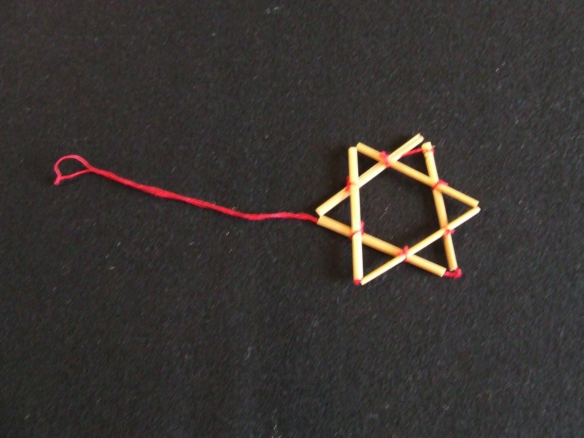 Stjärna av halm. Består av två sammanknutna trianglar. Ögla av rött bomullsgarn. Höjd och bredd 55 mm.