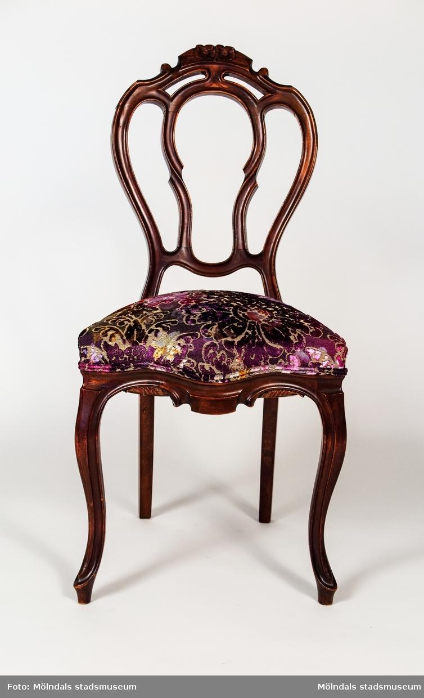 Stol, betsad björk, nyrokoko, genombruten rygg med kälning och två skulpterade blommor på krönet. Svängda framben. Fast stoppad sits med resårfjädrar. Stolen är tillverkad vid sekelskfitet 1900. Osignerad, men en vanlig modell som tillverkades av flera snickare i Lindome.  Inköpt på auktion 2010, stolen var då klädd i ett slitet rosa sidentyg. Omstoppad och omklädd med ett mönstrat tyg från Tricia Guild, 2013.