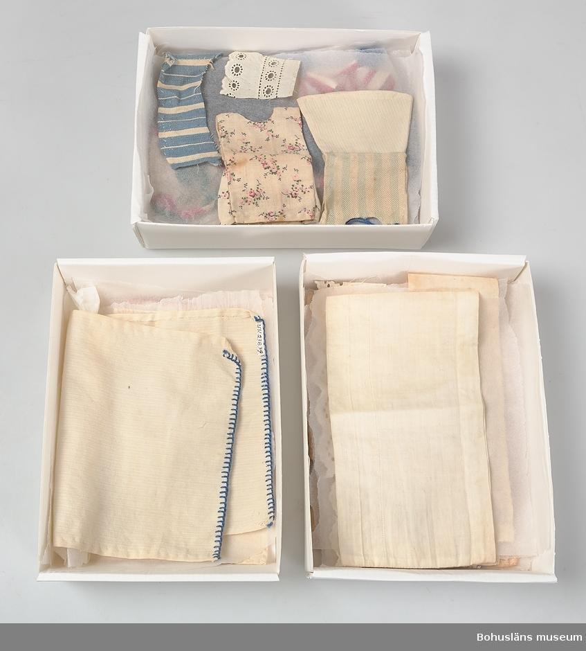 """Beige skolåda med påklistrad etikett varumärke och text """"Säfsjö Skofabriks A:B, Säfsjö Art 11939 läst 25 klack. Order No 194 storl 38 """"Skaft"""". Skrivet med blyerts """"Irma Bolin"""". Inuti lådan en garantisedel """"Vi garantera, att dessa skodon äro tillv. av bästa kvalite lackerat skinn"""".  Lådan innehåller en gråmelerad yllekappa med svart pälskrage, 58 klänningar i olika storlekar och färger, 5 kjolar i olika  färger och storlekar, 4 blusar i olika storlekar och färger, 4 lekdräkter i olika färger och storlekar. En grön väst. En stickad beige tröja. Två rutiga bomulls- och ett randigt flanellförkläde. En flerfärgad rutig schalett. 8 mössor i olika färger och former. Två jackor en ljusblå med svart pälskrage en grönrutig med svart pälskrage. 7 kuddar, 3 täcken, 6 gardiner, 2 dukar, 8 underlakan. Ett vitt överkast kantat med langettsöm i blått."""