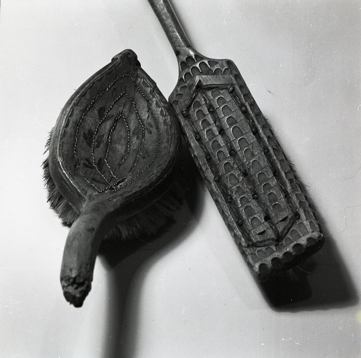 Två borstar med dekorativa målningar och sniderier på trähandtaget. På träet är trådarna som fäster borsten synliga.