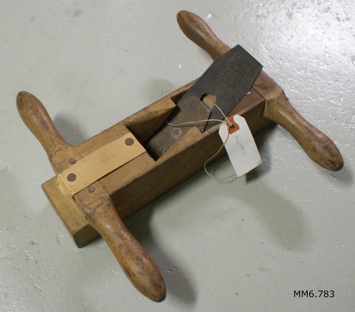 Oxhyvel av trä.  I centrum hål för skärstål och träkil. Med handtag fram- och baktill.