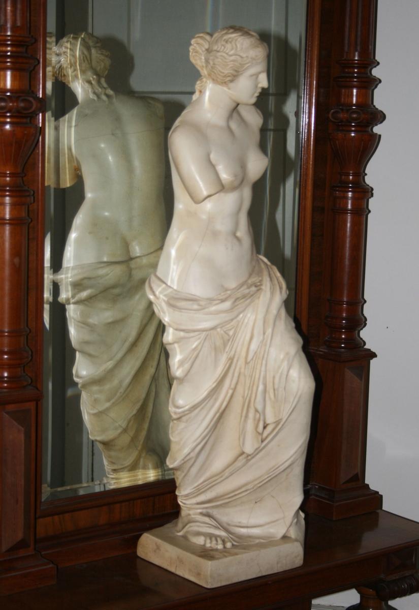 Stående kvinne med draperi fra hoftene og ned,  v. arm mangler, h. avslått i originalen i overarmen.  Bølgende bakoverskrøket hår med hårbånd, knute og nakkekrøller.