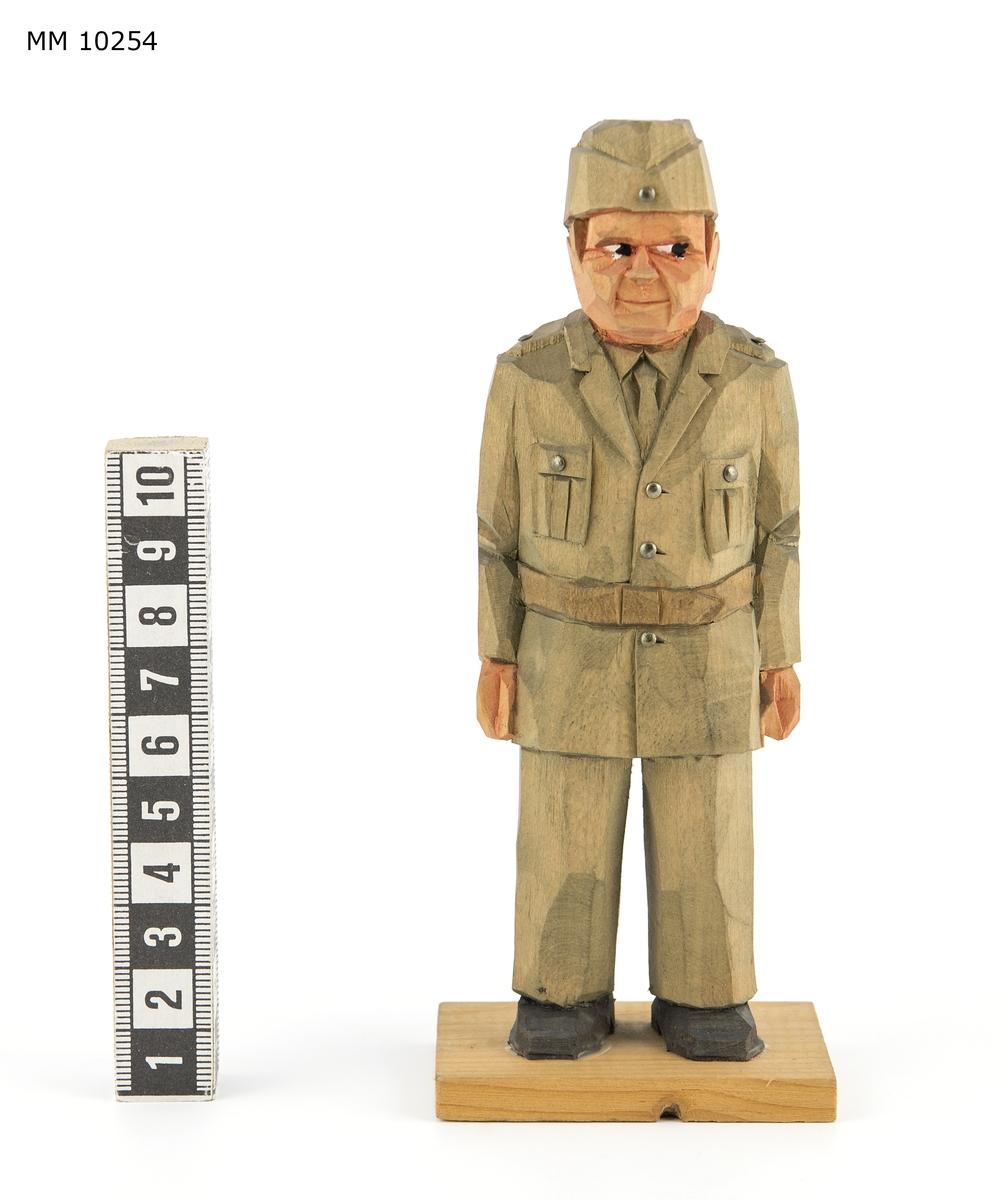 Skulptur. Föreställer en militär i uniform m/1942. Fastatt på en platta av trä.
