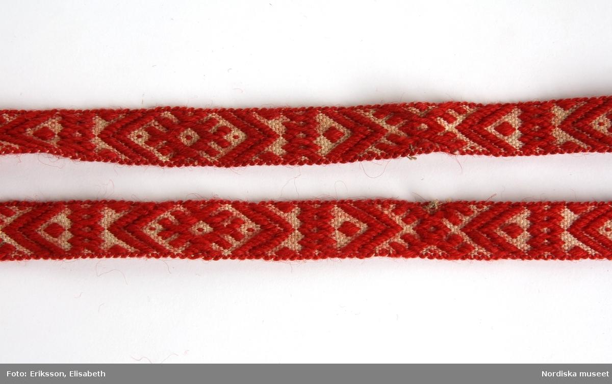 """Huvudliggaren: """"a-g Dräkt- och Slåtterutrustning fr. Södra Finnskoga sn., Elfdals hd., Värmland. För finne. Dräkten bestående af: a.1. Ylletröja, stickad af ullgarn i röda och hvita ränder. a.2. Byxor, svarta, af vadmal, med 10 mässingsknappar. a.3. Väst af rutigt ylletyg i rödt och brunt (med påsatta lappar af annat tyg). a4. Mössa, svart. a.5. 1 par ullstrumpor, grå, utam fötter. a.6. 1 par näfverskor. a.7. Lifbälte af svart läder med vidhängande tre knifvar och en syl i två slidor. a.8. 1 par knäband. L. 0,54 och 0,47. Väfda i rödt och hvitt. a.9. 1 par skinnvantar. Slåtterutrustningen bestående af: b. Näfverkont. H 0,63. B 0,56. Med ett inneliggande blad (se c). c. Lieblad. L. 0,815. Stämpl: 'N [ritat: två korslagda pilar omgivna av E och O och kring det en cirkel av prickar] LÅNGÖ FÖ'. d. Lie med skaft. Liens l. 0,705. Skaftets l. 1,335. Skaftet märkt 'P'. e. Räfsa. f. Saltflaska. H. 0,15. Af näfver. g. Saltflaska. H. 0,18. Af näfver. a. Kläderna mycket slitna och söndriga. d. Lien bräckt och lagad.""""  Utdrag ur bilaga: """"På Rottneros bruks utställning /Stockholmsutställningen 1897/ har jag placerat en finngubbe som skulle framställa skördeverktygen förr till jemförelse med dem som  nu användas, och som tillverkas här. Denna gubbe har jag tänkt att skänka till Nordiska museet."""" (brev från brukspatron H.E.Montgomery , 25/9 1897)  Dräkt- och slåtterutrustning A-G, där A.1 - A.9 är en dräkt för en """"finngubbe"""".  A.1 Ylletröja stickad, med röda och vita ränder A.2 Byxor, av svart vadmal med 10 mässingsknappar A.3 Väst av rutigt ylletyg i rött, grönt och brunt, lappad med annat tyg. A.4 Mössa svart A.5 1 par grå yllestrumpor utan fötter A.6 1 par näverskor A.7 Livbälte av svart läder med vidhängande tre knivar och en syl i två slidor. A.8 1 par knäband vävda i vitt och rött A.9 1 par skinnvantar. Huvudliggaren: """"Kläderna mycket slitna och söndriga"""". A.9 Tumvantar av skinn, längd 28 cm, bredd 16 cm, ovansida av vitt krulligt lammskinn, insida av mörkbrunt pälsskinn, för"""