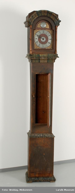 Form: høy,smal kasse, noe større øverst og nederst smal dør foran lodd og pendel.