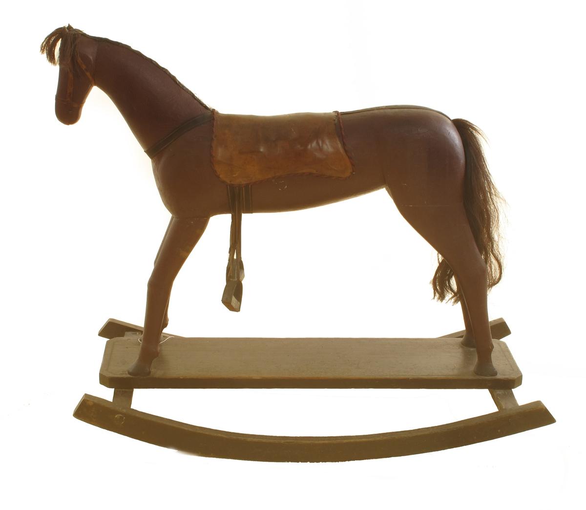 Gyngehest skåret i tre og malt rødbrun. Halen og manen er av hestehår, sadelen av skinn,  stigbøylene er falt av og henger i et tau på siden, tømmer og bjelle. Dessuten hører det  til en ridepisk. Hesten står på meier av tre.