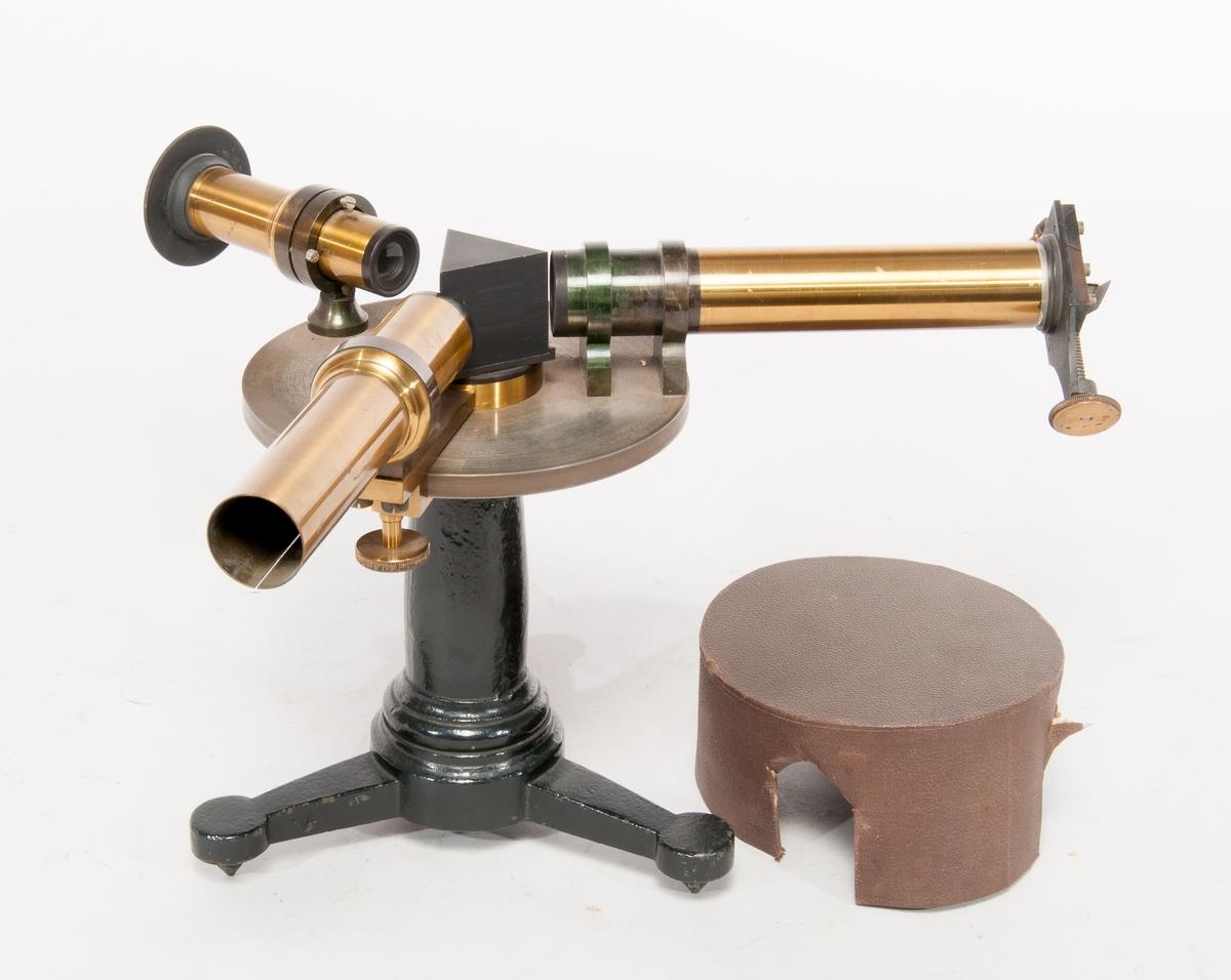 Spektroskop på fot av gjutjärn, med prisma och tuber av mässing. Skyddshuv av papp, med notering på insidan i blyerts: John Hertzberg.