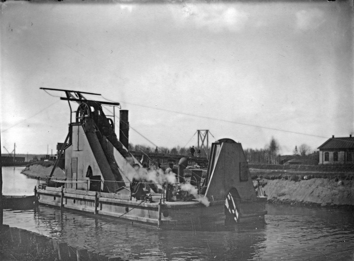 Köpings stads mudderverk, tillverkat år 1898 sålt år 1970. Muddringsverket ses i aktion i övre hamnbassängen. Till höger syns en del av det rivna lokstallet.