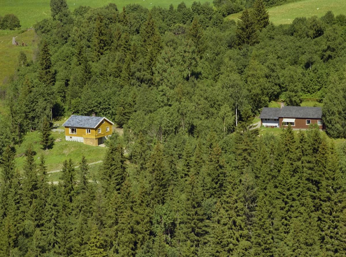 To atskilte bolighus. Gul-brunt med kjeller t.v. og brunt med garasjetilbygg t.h. i bildet. Lauv-og barskog. Åker i bakgrunn.