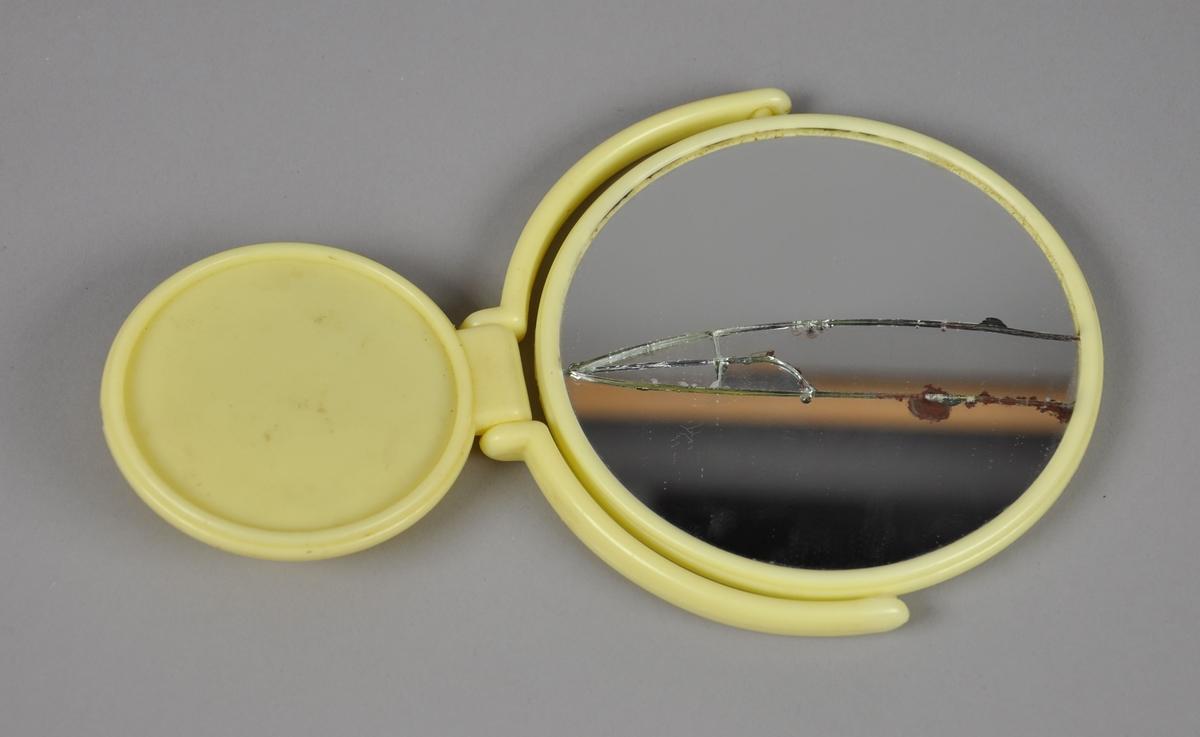 Rundt sminkespeil med justerbart understell av gul plast. Det er speil på fram- og bakside, speilet på én av sidene er sprukket opp.