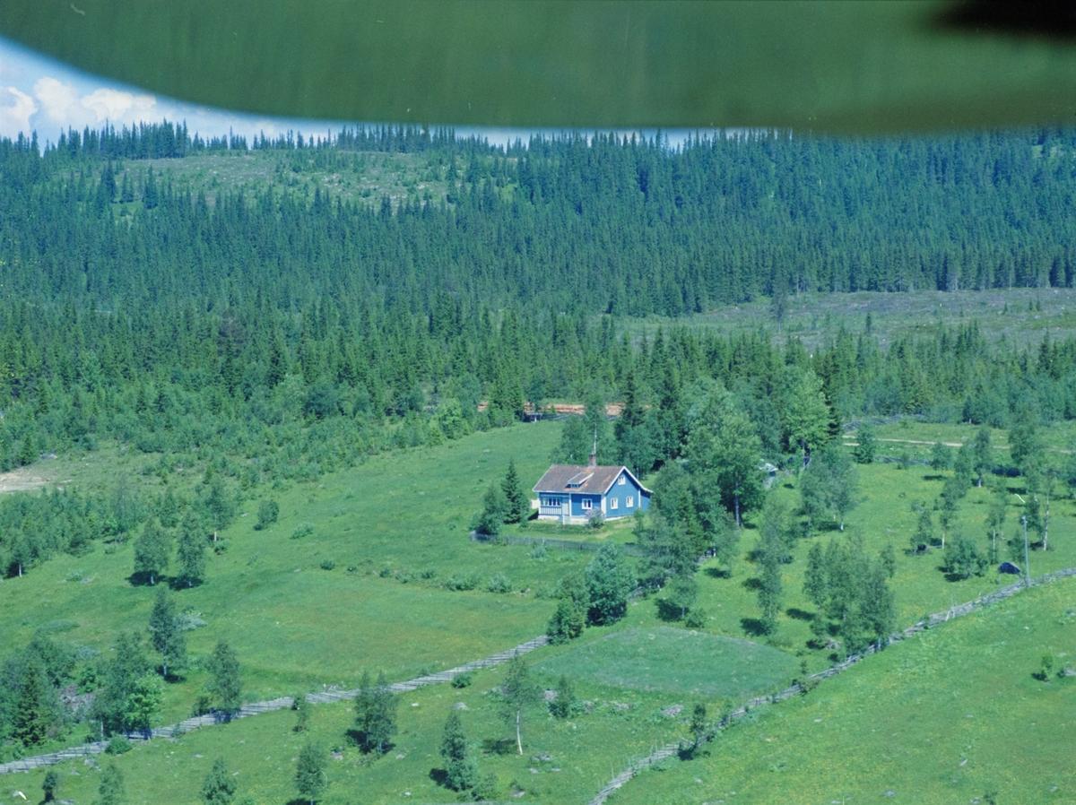 Flyfoto, Lillehammer, bebyggelse. Åsheim, adresse Åsstuevegen 160. Lyseblått, en og enhalvetasjest hus med hvite vinduskarmer. Inngjerdet og en bygning skimtes bak trærne på eiendommen. Beitemark og granskog rundt.