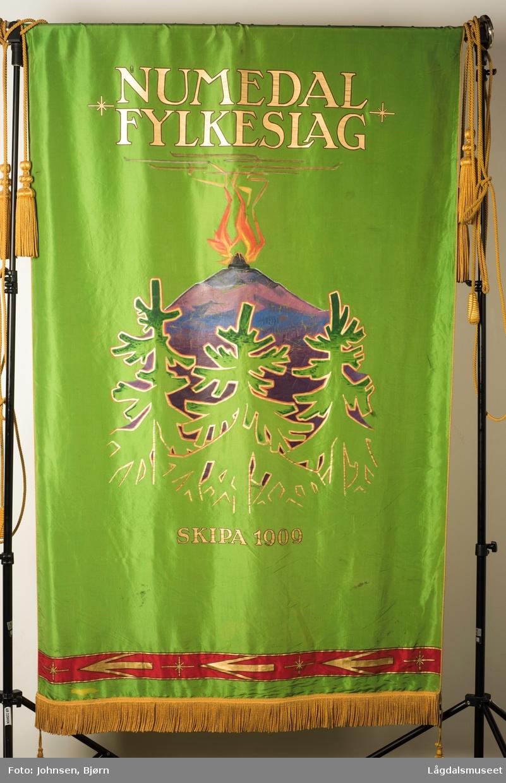 """s 1: Påskrift: """"NUMDEDAL FYLKESLAG SKIPA 1909"""". Motivet viser et fjell med en brennende varde og skog.  s 2: Påskrift: """"Du Numedal du vene med fagre fjell og fjord"""". Motivet på baksiden er to akantusranker."""