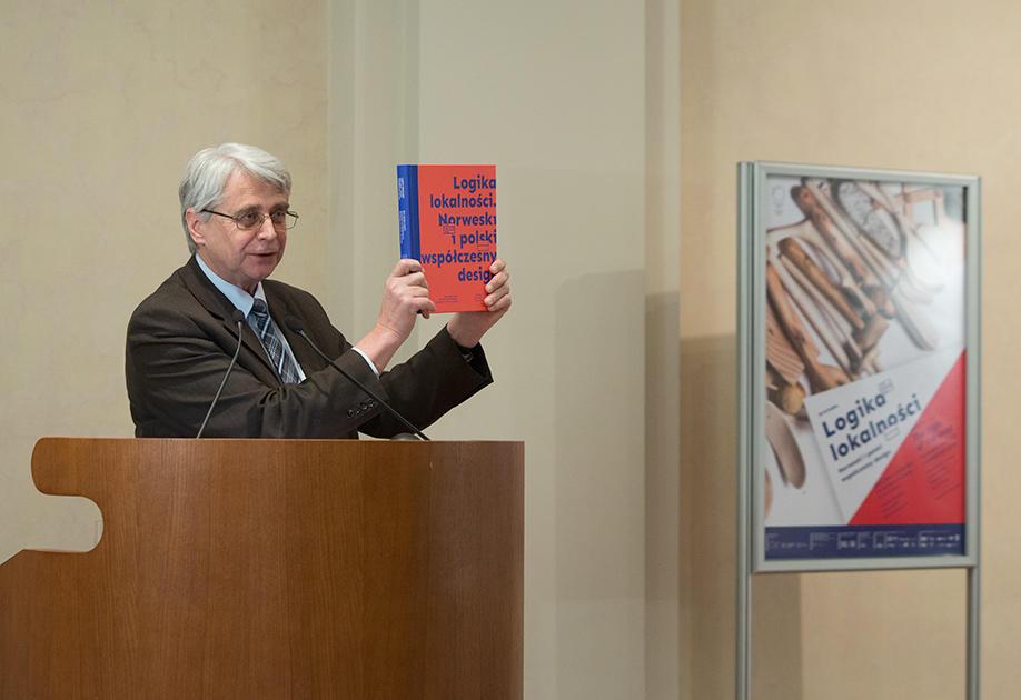 Prof. Dr. Jacek Purchla, direktør ved ICC, står bak talerstolen og holder opp utstillingskatalogen på åpningen av Logika Lokalnosci, 16. desember 2016. Plakaten for utstillingen sees i bakgrunnen.