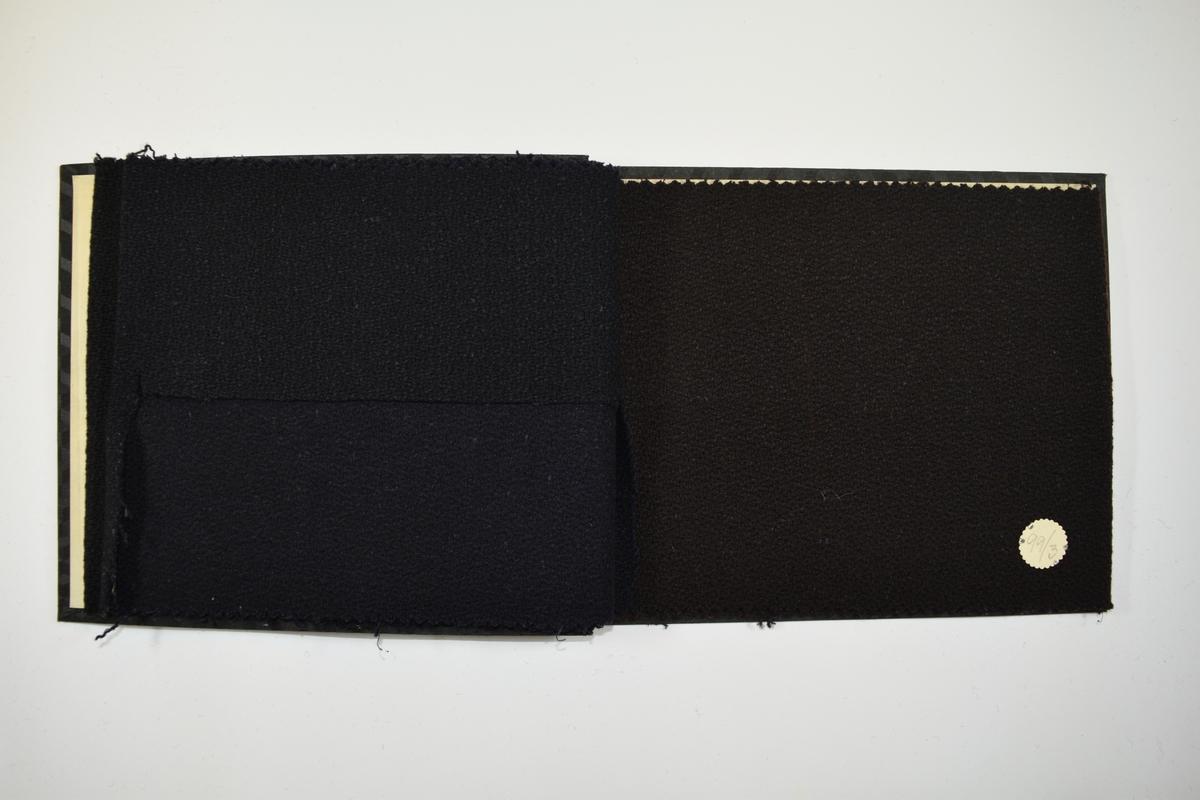 Prøvebok med 3 prøver. Middels tykke ensfargede stoff. Stoffene ligger brettet dobbelt slik at vranga dekkes. Stoffene er merket med en rund papirlapp, festet til stoffet med metallstift, hvor nummer er påført for hånd.    Stoff nr.: 99/1, 99/2, 99/3.