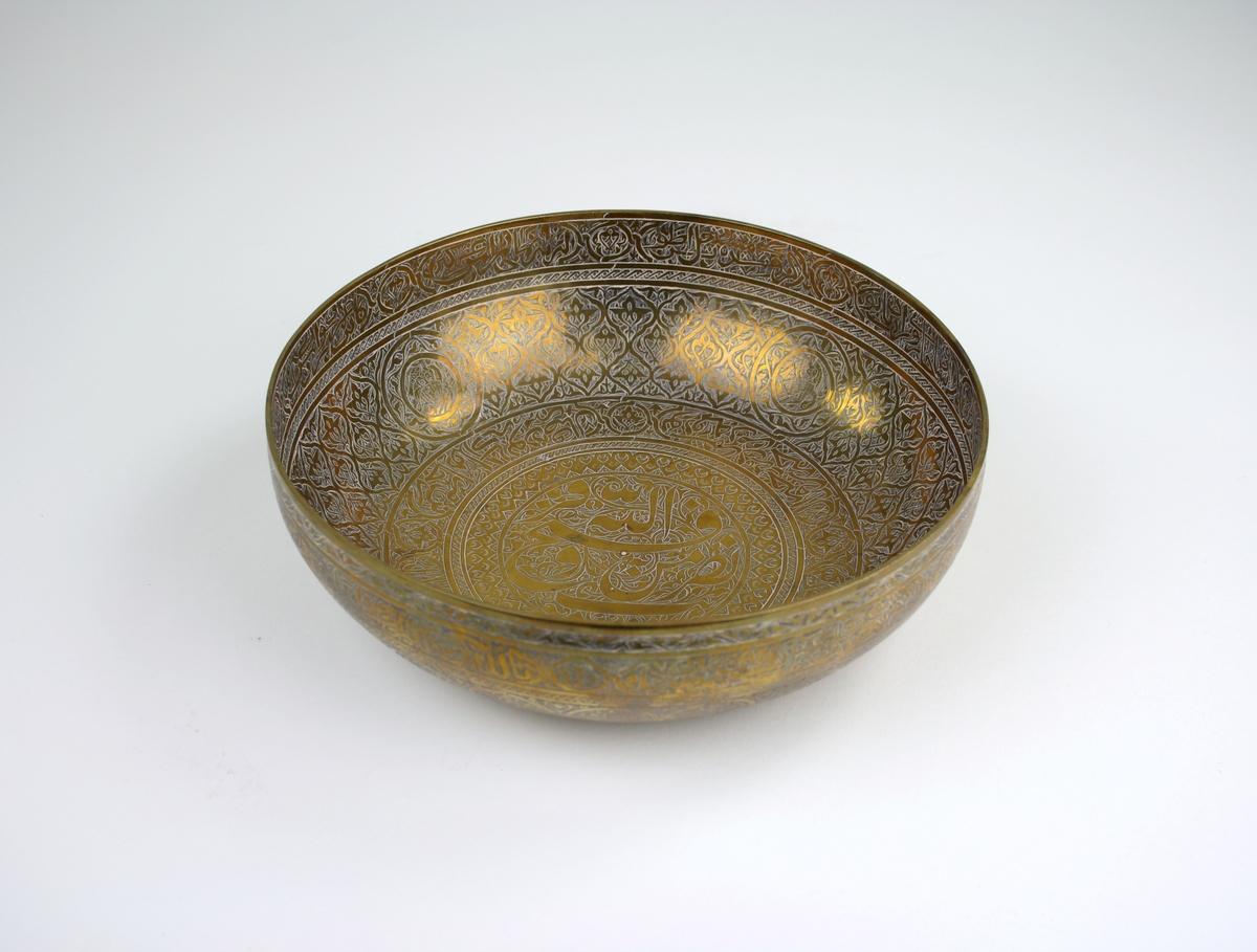 Skål av mässing med graverad dekor.Enligt notering från Persien. På skålen finns både arabisk och persisk skrift. Det är citat ur koranen (Med hjälp av gud är segern nära) och en persisk dikt.