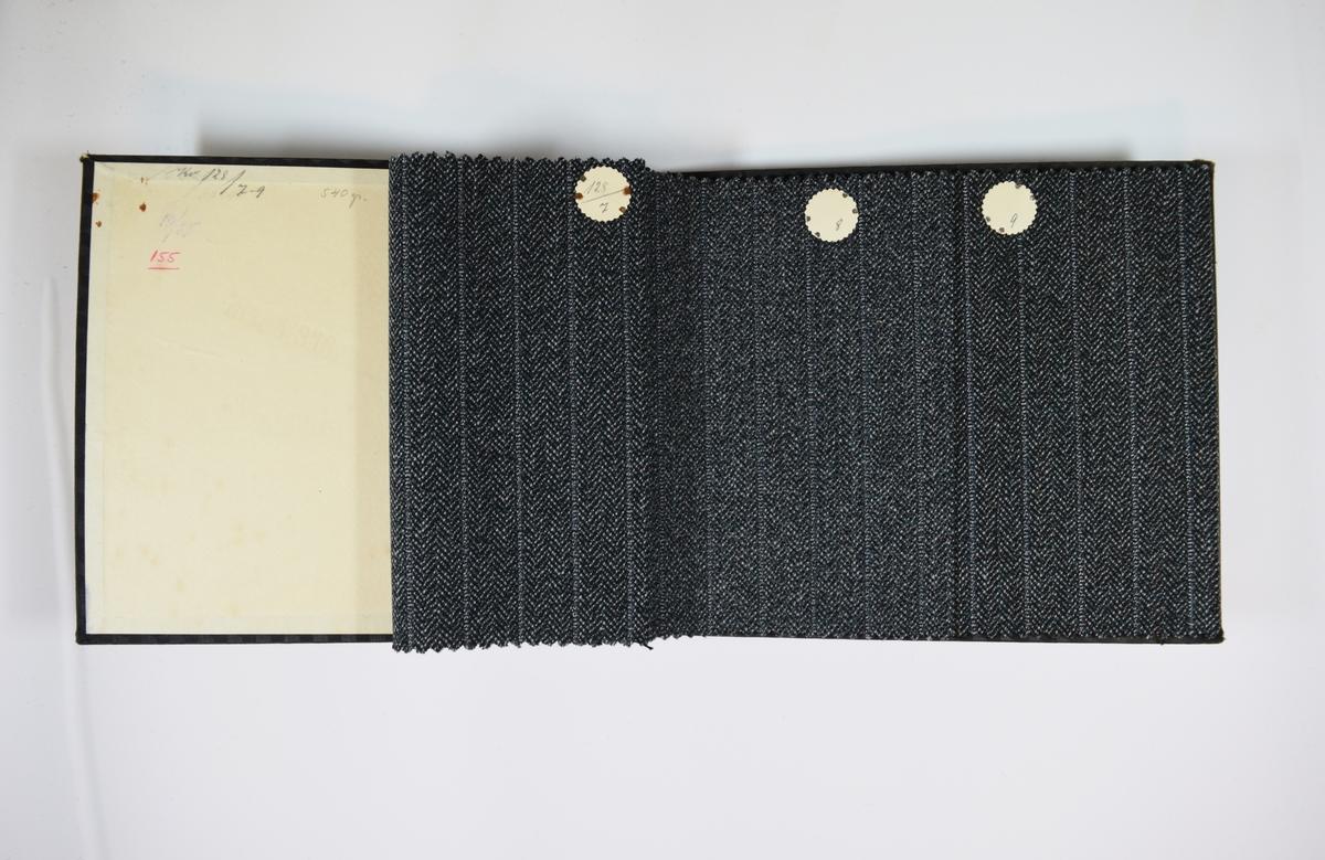 Prøvebok med 6 stoffprøver. Middels tykke stoff med fiskebensmønster og/eller striper. Stoffene ligger brettet dobbelt i boken slik at vranga dekkes. Stoffene er merket med en rund papirlapp, festet til stoffet med metallstift, hvor nummer er påført for hånd. Innskriften på innsiden av forsideomslaget indikerer at alle stoffene har kvalitetsnummer 128.   Stoff nr.: 128/1, 128/2, 128/3, 128/4, 128/5, 128/6.