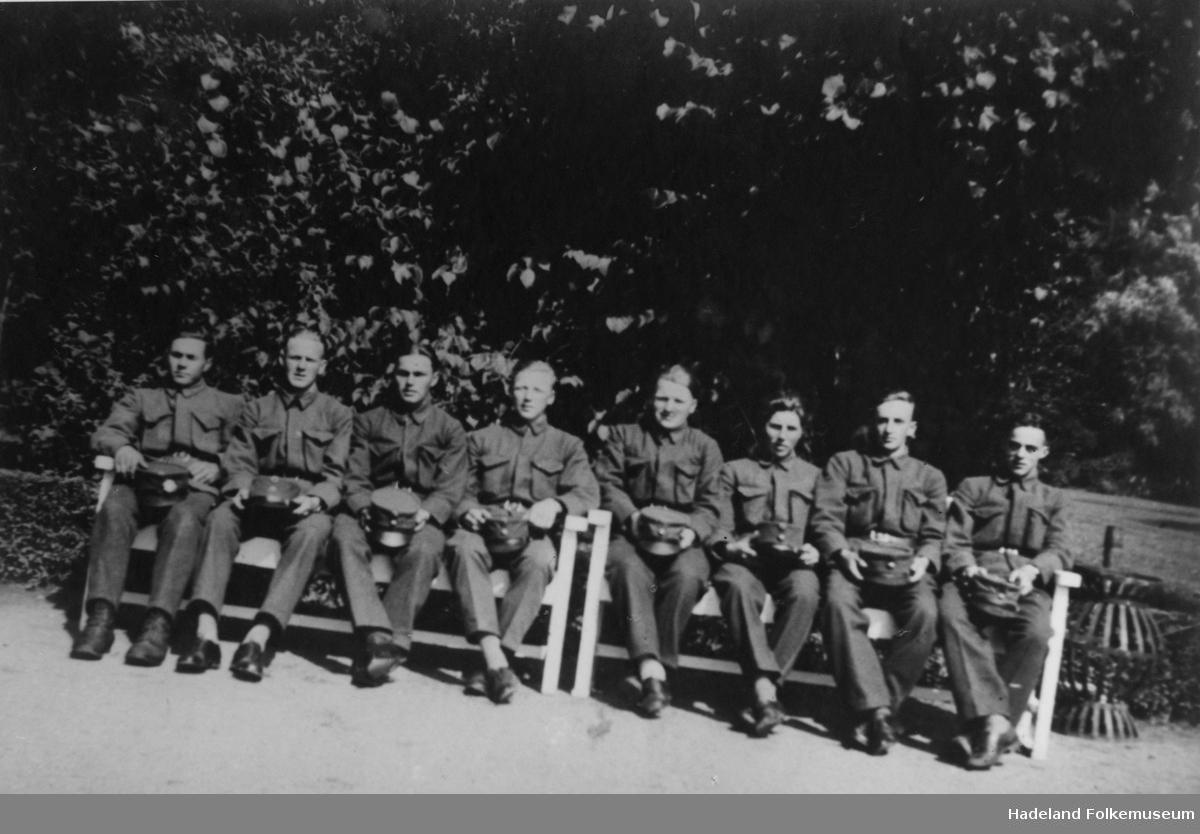 8 menn i uniform sitter ute på 2 benker.