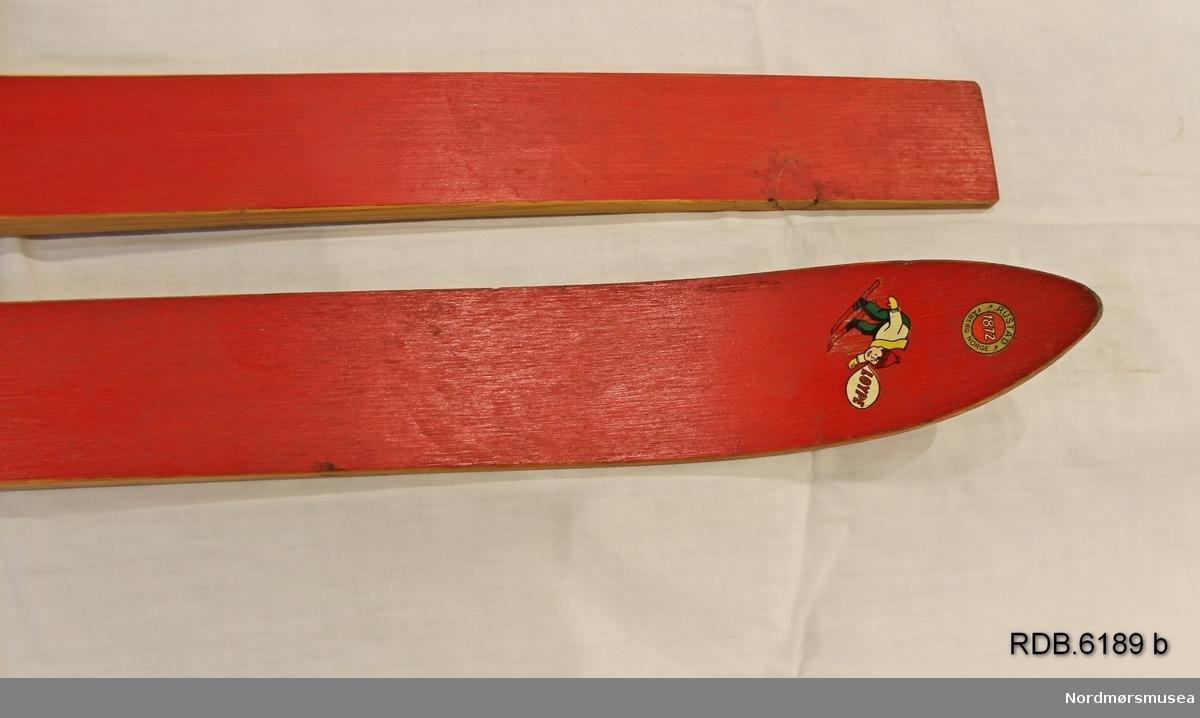 To røde, ubrukte barneski fra Rustad skifabrikk. Skiene har ulik lengde og er uten bindinger. Bred, lav skibrett, rød overside, trekvite kanter og såle med 1 styrerand. Rustadlogo på skituppen og bilde av barn som står på ski foran skibretten. Skiene har stått i utstilling i fabrikken.