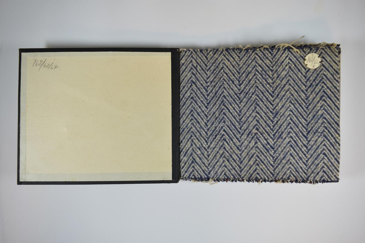 Prøvebok med 6 stoffprøver. Middels tykke to- eller flerfargede stoff med fiskebensmønster. Stoffene ligger brettet dobbelt i boken. Stoffene er merket med en rund papirlapp, festet til stoffet med metallstifter, hvor nummer er påført for hånd. Innskriften på innsiden av forsideomslaget indikerer at alle stoffene har kvaliteten 162.   Stoff nr.: 162/62, 162/63, 162/64, 162/65, 162/67.