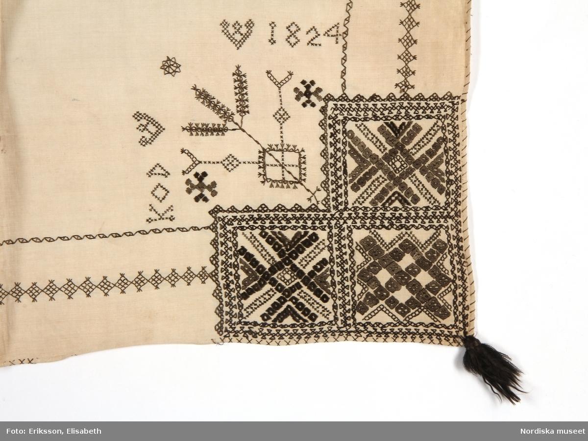 """Halskläde av tuskaftat fint linne. Kvadratisk form, avsett att vikas i tresnibb, broderad i tre hörn i  svartstick. Broderierna är utförda i svart silke. Mönstren är geometriska men oregelbundna. Bård av rombiska former i förstygn  med tofssöm mellan huvud- och hörnmotiv. Sömsätten i broderierna är  rätlinjig plattsöm, förstygn, efterstygn, flätsöm, korssöm och tofssöm. Svarta silkestofsar i alla hörn. Broderad märkning i korssöm: """"KOD 1824"""" vid huvudmotivet. I det ovikta hörnet är huvudmotivet placerat, detta upprepas sedan halverat på båda snibbarna. Fållen översydd med kastsöm i kryss i svart silke runtom alla sidor, delar av kastsömmen bortnött. Den del som inte var synlig utåt är odekorerad. Anm: Fläckigt i mittvikningen.  Svartstick är ett broderi som förekommer i några socknar runt södra Siljan i Dalarna. Det broderas som dekor på vita halskläden till folkdräkten. Halsklädet bars till högtidsdräkten - kyrkdräkten, och användes i högmässan vid de stora helgerna och bröllop.  Utdrag ur Odstedt Ella, (1953), Övre Dalarnas bondekultur under 1800-talets förra hälft. 4.Folkdräkter i övre Dalarna. Sid 9:"""" Toppa (=tofs o.d.) är formen för det i dialekterna allmänna 'tuppa'. I ordet topphalskläde får man således känna igen dialektens 'tuppassklä', alltså 'halskläde med tofsar i hörnen'. """" Sid 305: """"Topphalsklädet (svartstickklädet) var det förnämsta och användes vid de största högtiderna, då man gick tröjlös och då gul raskmagd ej bars, samt därjämte på bröllop och vid kyrkotagning efter första barnet, då det bars av både modern och hennes följeslagerska, allt den tid man var tröjlös."""". Sid 497: """"Småkullorna hade samma halskläde som de vuxna t.o.m. i ett mindre format det silkesstickade topphalsklädet, om sådant hörde till dagen."""" Lästips: Maria Björkroth. (1982). """"Svartstick"""". Textil tradition, s. 105-121.  /Inga-Lill Eliasson 2007-02-23"""