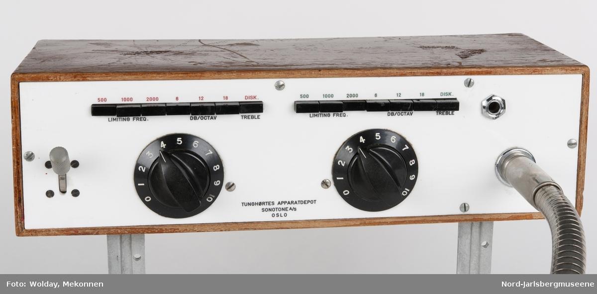 Rektangulær apparat i tre med frontdeksel. Reguleringshjul og mikrofon på fremsiden Knapper for lydregulering Påsatt vinkeljern for feste i bordplate