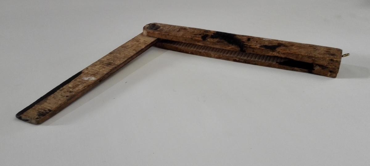 Lausvinkel av tre, klinka saman med jarnnagl. På begge sider den korte armen og påbegge sider i spalta i den lange armen er innskorne strekar med 0,6 cm mellomrom.