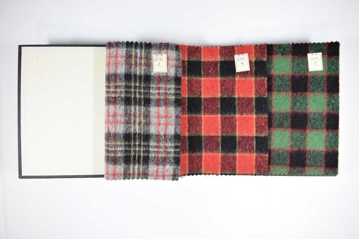 Prøvebok med 3 stoffprøver. Middels tykke stoff med flerfarget rutemønster. Alle prøvene er laget med toskaftvev (tydelig fra stoffenes bakside, mens oversiden er dekket av fibre), men fargene og mønsteret varierer mellom stoffene. Stoffene ligger brettet dobbelt slik at vranga skjules. Stoffene er merket med en firkantet papirlapp, festet til stoffet med metallstifter, hvor nummer er påført for hånd.   Stoff nr.: 600/3, 600/4, 600/5.