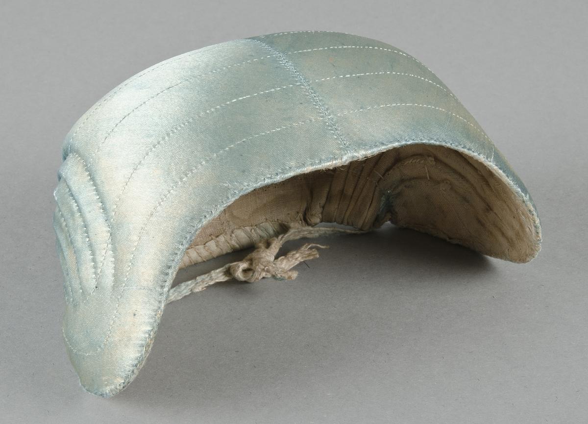 Bindmössa av ljusblått siden. Foder av linnelärft. Knytband i nacken av linneband.