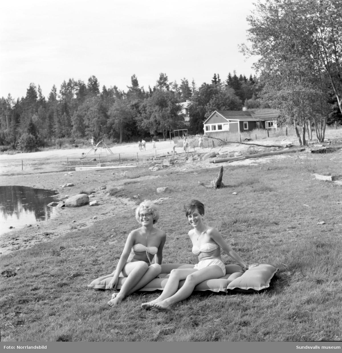 Två unga kvinnor vid en badvik med strand och klippor i Söråker.