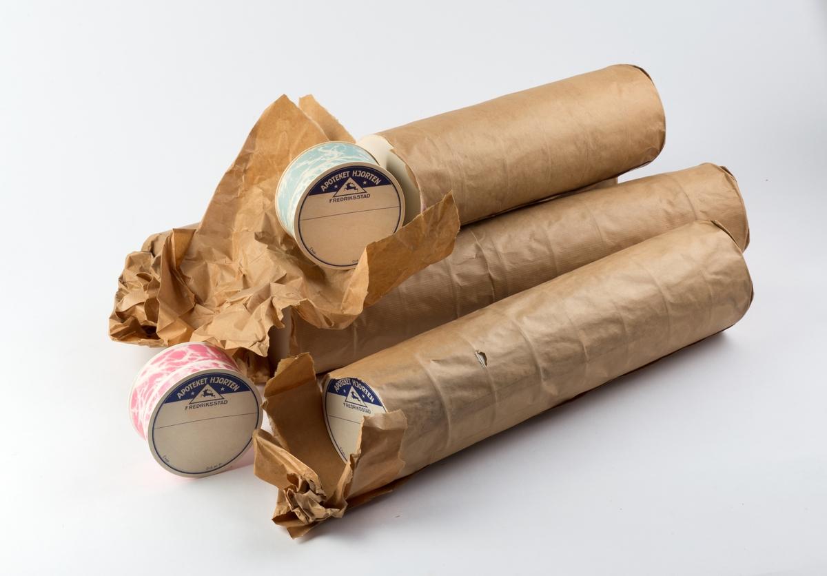 Runde pulveresker i engrospakning, 4 ruller som alle er delvis åpnet. 3 ruller inneholder hver 9 esker, en har bare 7 esker. Alle har samme diameter men litt forskjellig høyde.