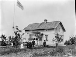 Män, kvinna och barn i trädgården vid bostadshus, Börstil so