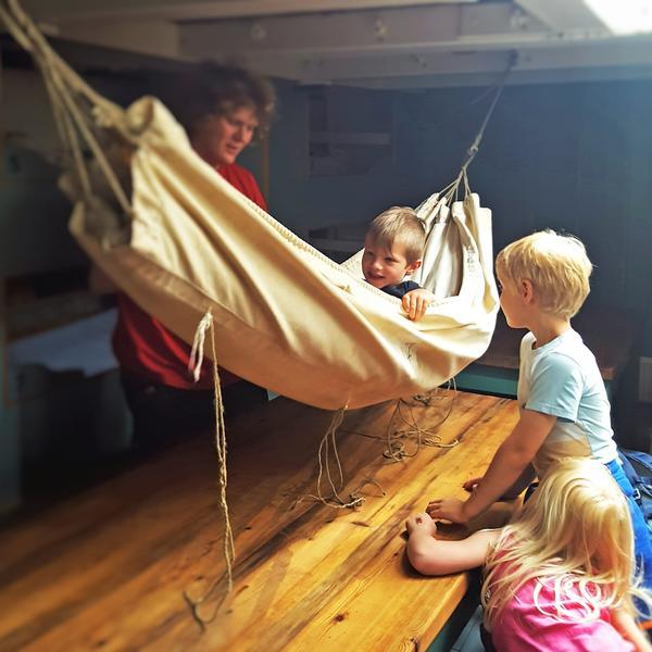 Hengekøye ombord skip, ett barn i hengekøya, to barn utenfor, én voksen bak.. Foto/Photo
