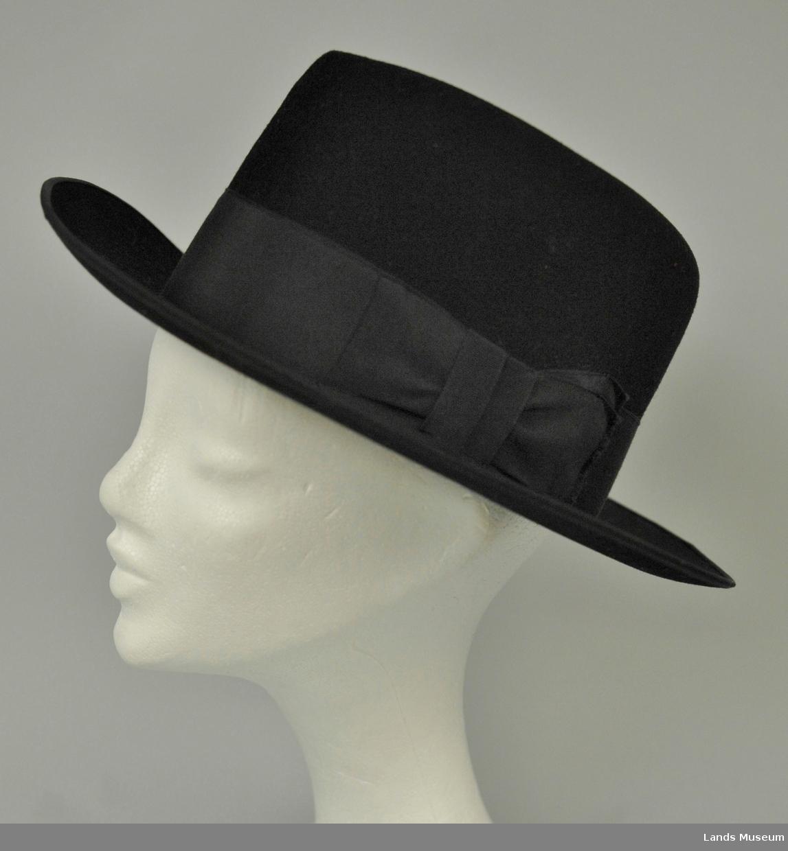 """Hatten har høy pull. Bredt sort ripsbånd rundt pullen. Lyst brunt skinn i svettebrem innvendig. Lite brukt. """"Penhatt""""."""