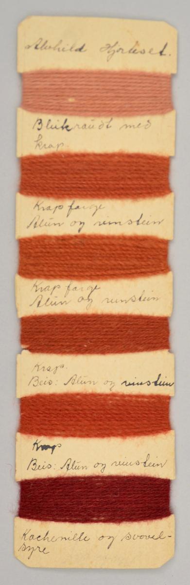 Pappbit der det er surra rundt ulltråd i ulike raudlege fargar i seks ulike felt. Under kvar farge står det skrive kva som er brukt for å lage fargen.