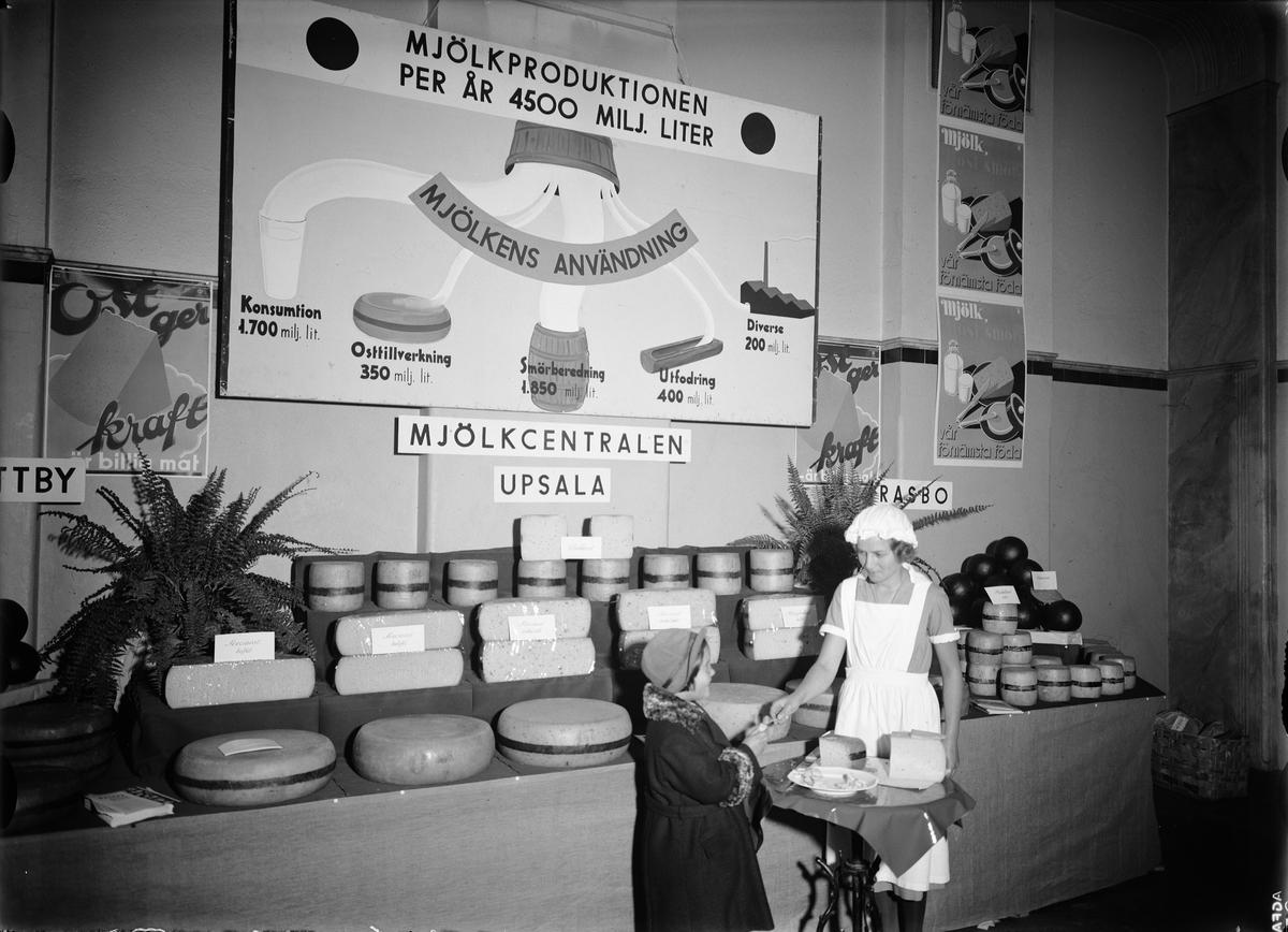 Mjölkcentralens utställning på livsmedelsmässa arrangerad av Hushållningssällskapet och Upsala läns husmodersförbund, sannolikt på Norrlands nation, Västra Ågatan
