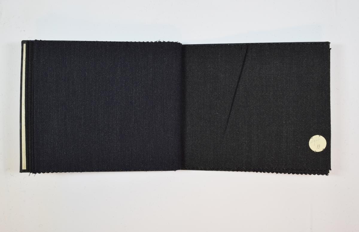 Rektangulær prøvebok med 6 stoffprøver og harde permer. Permene er laget av hard kartong og er trukket med sort tynn tekstil. Boken inneholder middels tykke, mørke stoff med diskret striper eller fiskebensmønster. Stoffene er merket med en rund papirlapp, festet til stoffet med metallstifter, hvor nummer er påført for hånd. Innskriften på innsiden av forsideomslaget indikerer at alle stoffene har kvalitetsnummer 2000.   Stoff nr.: 2000/9, 2000/10, 2000/11, 2000/12, 2000/13, 2000/14.