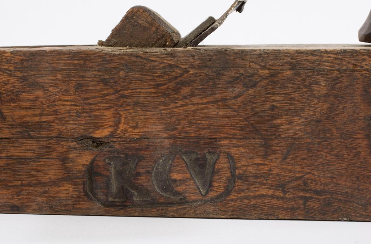 """Høvel i tre med to horn/håndtak, kile og dobbelt høveljern. På begge langsidene er det brent inn merket """"K, merket for sølv, V"""". Merket for sølv er speilvendt. I tillegg er det en påklistret lapp hvor det står: """"H""""vvel"""" eier Bergverksmuseet."""