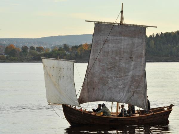 Trebåten Vaaghals på vannet med to seil, minst fem personer ombord, kveldssol, land i bakgrunnen.. Foto/Photo