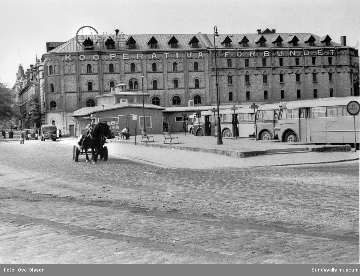 """Text: """"Busscentralen vid Nybrogatan och hamnen, centrum för landets kanske tätaste busslinjer"""". I förgrunden uppställda bussar och busstationsbyggnaden, i bakgrunden magasinskvarteret Briggen och bebyggelsen längs Nybrogatan."""