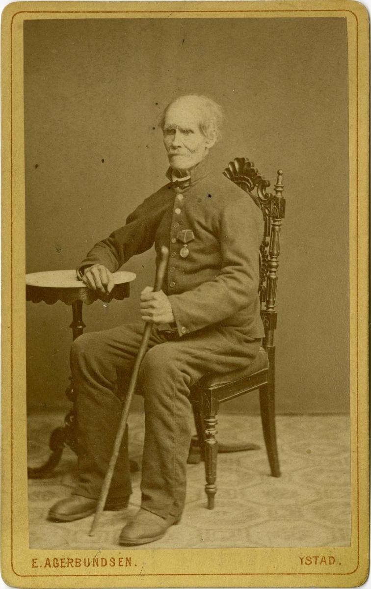 Porträtt av Nils Wakt, fd soldat no. 24 vid Herrestads kompani, Södra skånska infanteriregementet I 24. Belönad med Svärdsmedaljen. Avsked vid generalmönstringen 2/6 1853.