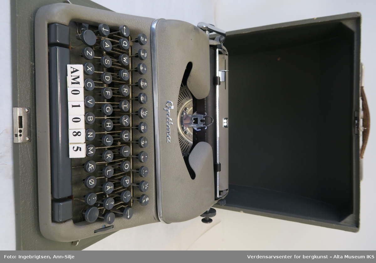 Reiseskrivemaskin med koffert. Denne maskinen er festet på en treplate. Både platen og kofferten er laget i tre som er kledd med et belegg. Håndtaket på kofferten er laget av lær.