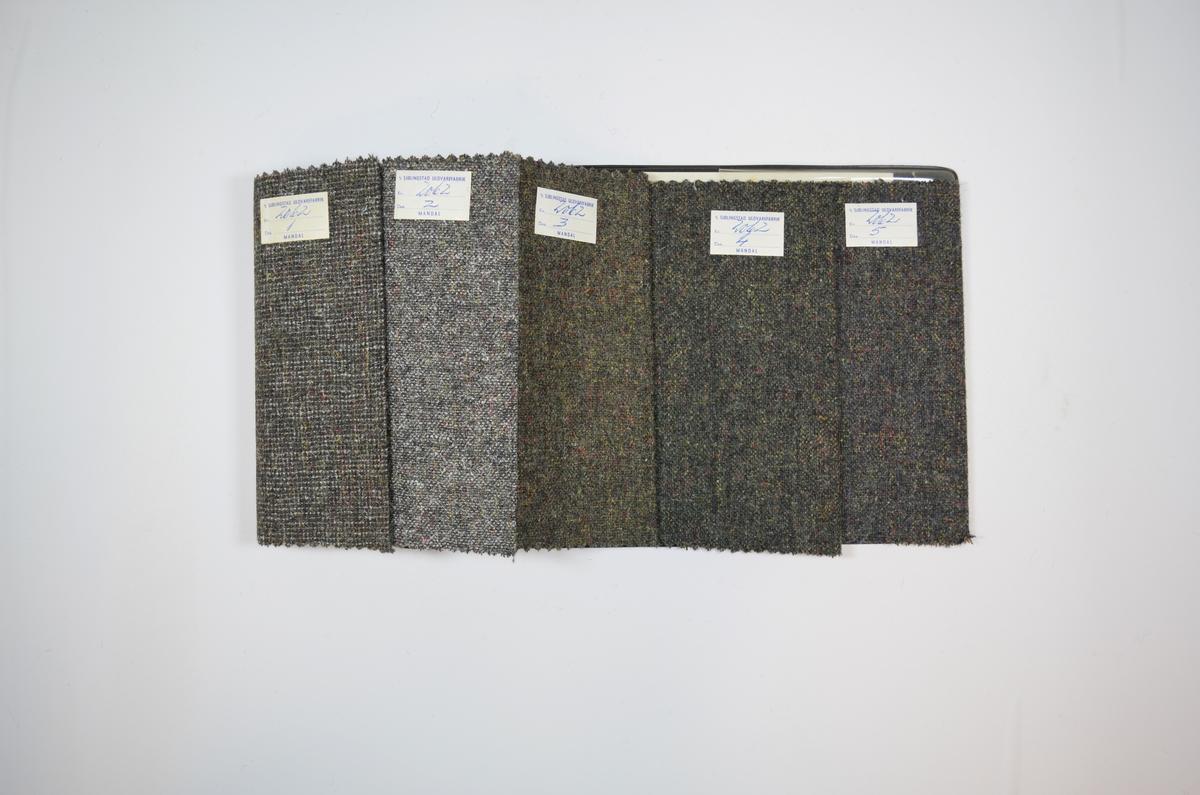 Prøvehefte med fem prøver. Middels tykke stoff bestående av flere farger jevnt fordelt. Noen av trådene har glansfult/metallisk utseende. Stoffene ligger brettet dobbelt i heftet. Stoffene er merket med en firkantet papirlapp klistret til stoffene, hvor nummer er påført for hånd i et trykket skjema. Heftet har stiv bakplate og en papp-plate der heftet er stiftet som dekker ca. 5 cm forsiden. I en plastlomme på innsiden av bakplaten er det en papirlapp med informasjon om stoffet, hvor det blant annet kommer frem at stoffene egner seg til gutte- og herrejakker.   Stoff nr.: 2062/1, 2062/2, 2062/3, 2062/4. 2062/5.