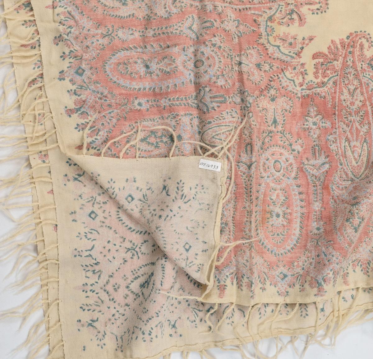 Sjal i gulkvit ullmusselin med trykt mønter, for det meste i rosa. Påsette kvite ullfrynser. Tverrendane er falda med tråklesting, to sider har jarekantar.