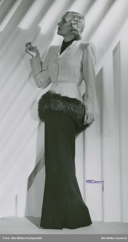 Modell i kavaj med pälskant och långklänning.