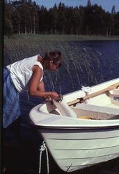 Antikvarie Kerstin Olsson med en kartrulle vid en båt på Kyn