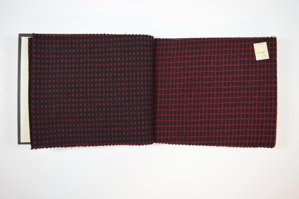 Rektangulær prøvebok med harde permer og seks stoffprøver. Permene er laget av hard kartong og er trukket med sort tynn tekstil. Boken inneholder relativt tykke stoff med flere typer rutemønster/prikker. Toskaftbinding. Stoffene ligger brettet dobbelt i boken slik at vranga skjules, men mønsteret er det samme på baksiden. Stoffene er merket med en firkantet papirlapp, festet til stoffet med metallstifter, med nummer påført for hånd.  Stoff nr.: 6008/6, 6008/7, 6008/8, 6008/9, 6008/10, 6008/11.