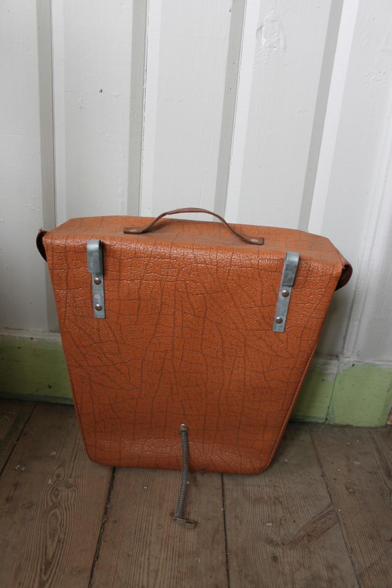 Brun väska i konstläder med äkta läderhandtag, läderkant och läderremmar i mörkare brun färg. Två metallspännen på framsidan och metallkrokar och metallfjäder på baksidan. Naturfärgad rottinginsida, delvis klädd med grå masonit.