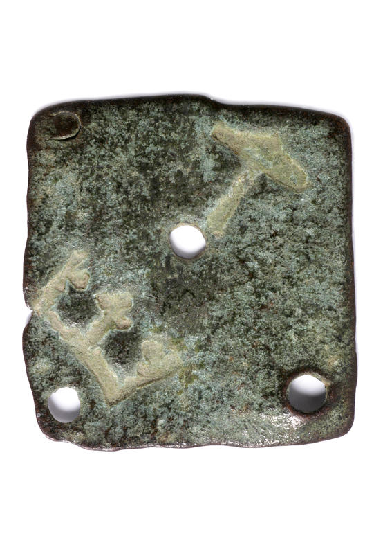 Et flatt og plateformet vektlodd med en krone og hammer stemplet inn.
